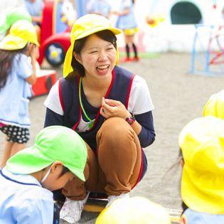 広い園庭でこども達がのびのびと遊んでいる幼稚園